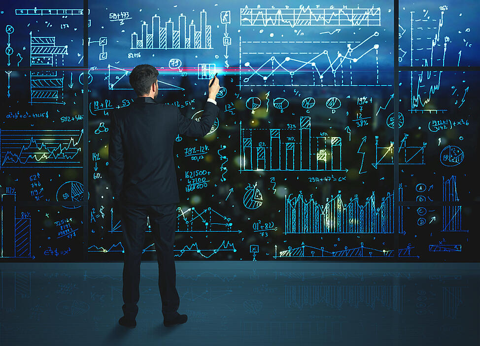 Businessman drawing business statistics on glass wall